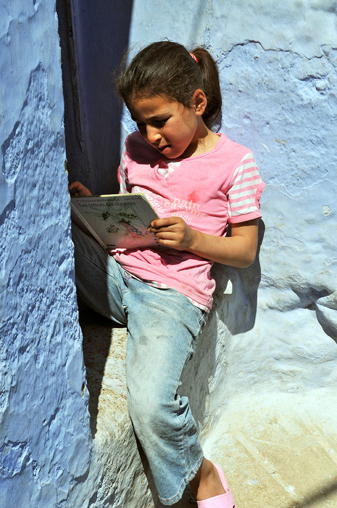 Rapariga a ler nas ruas de Chefchaouan