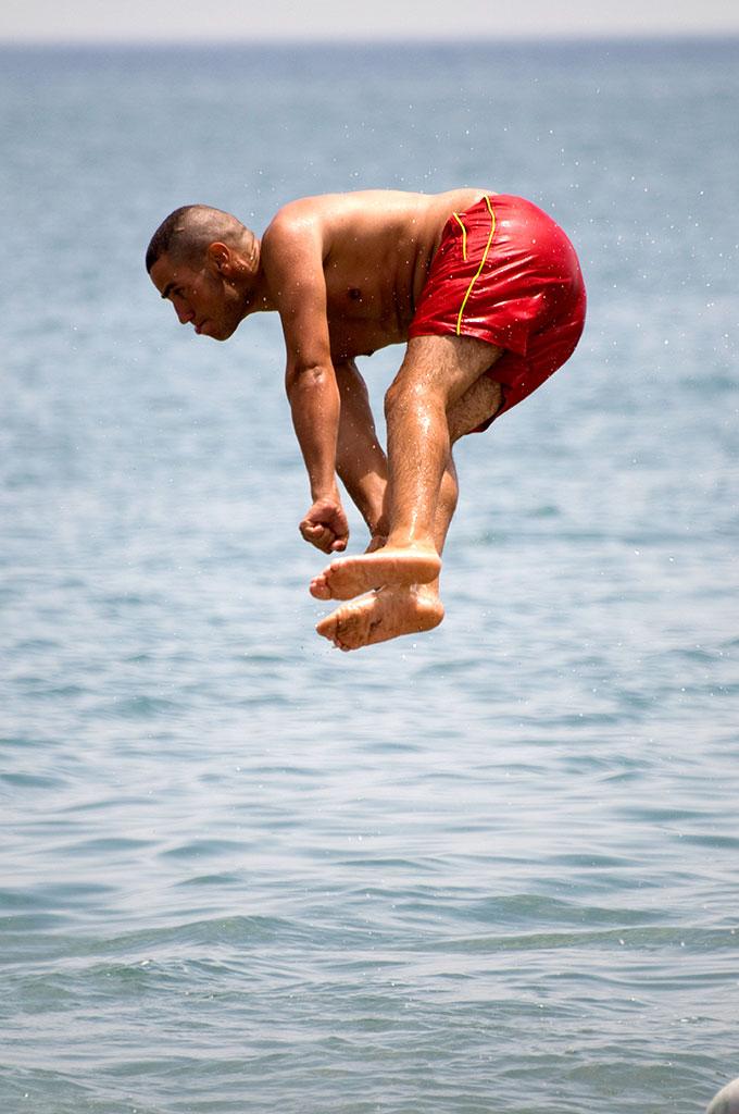 jovem acrobata na praia