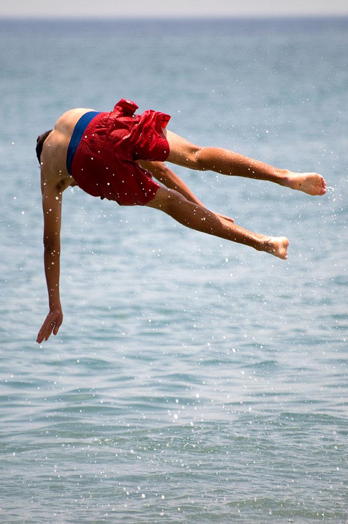 Jovem de Tetouan a fazer acrobacia na praia