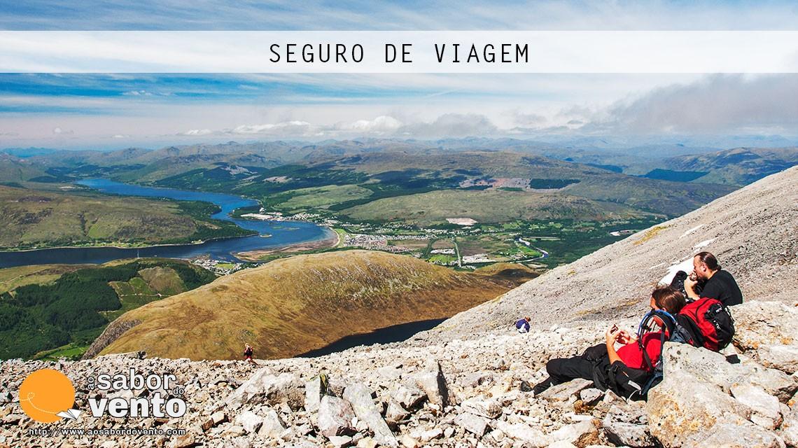 Montanhistas a descansar numa no topo de uma montanha, salvaguardos por um seguro de viagem.