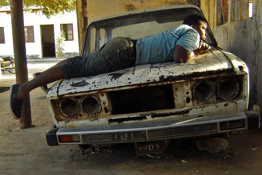 rapaz sobre carro velho na ilha de Moçambique