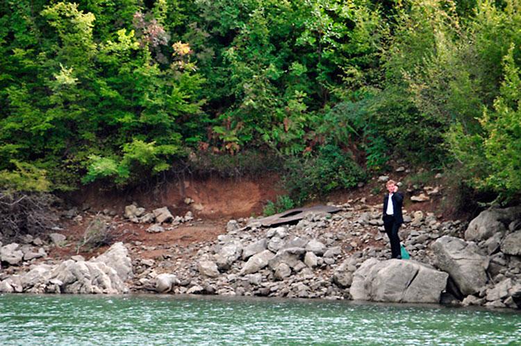 homem ao telefone junto ao lago