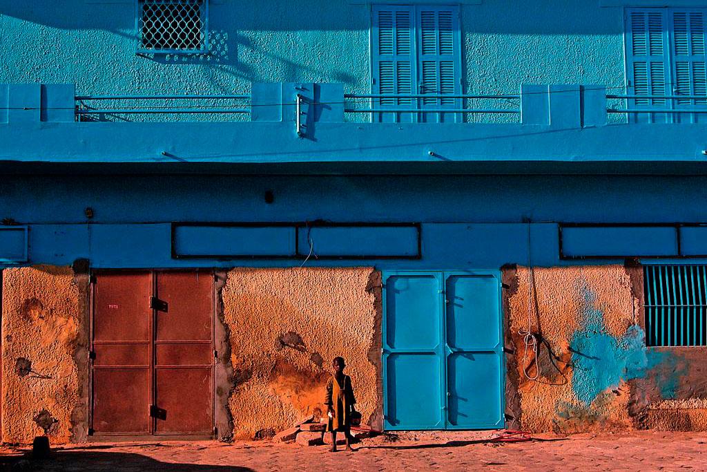 criança africana junto a edifício colorido