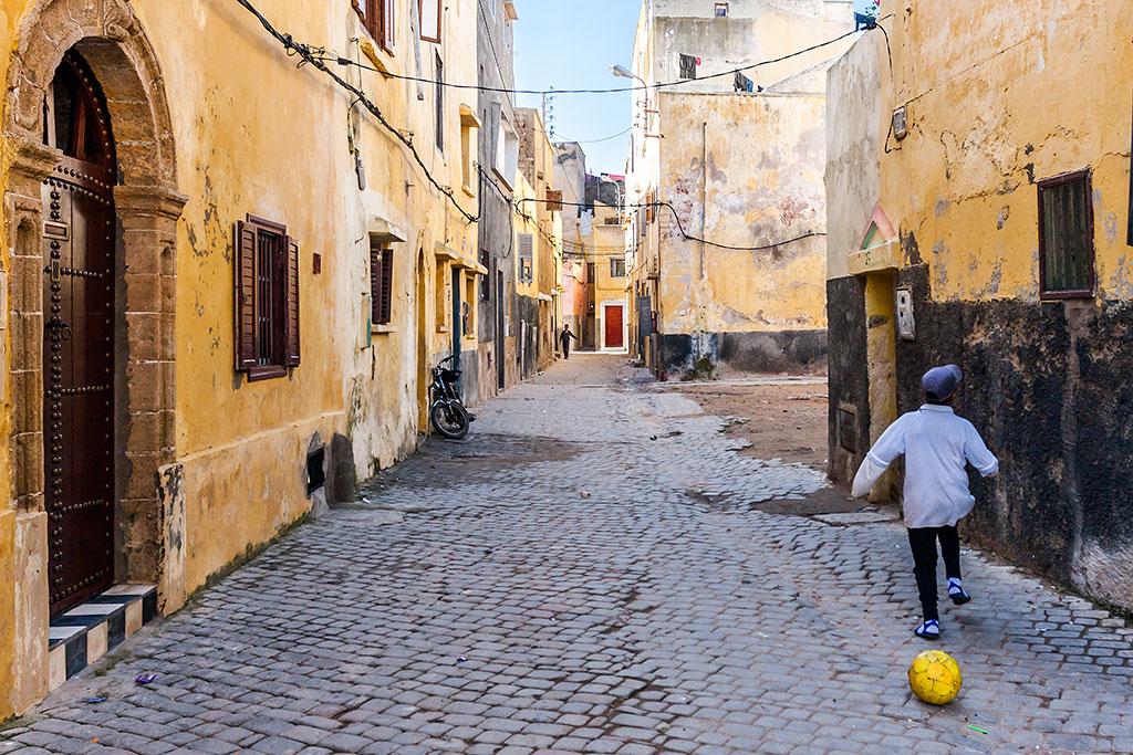criança a jogar à bola nas ruas de mazagão