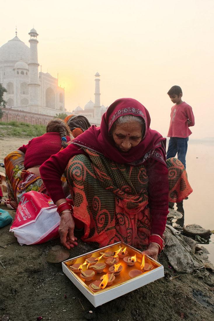 Mulher no rio Yamuna com Taj Mahal no fundo