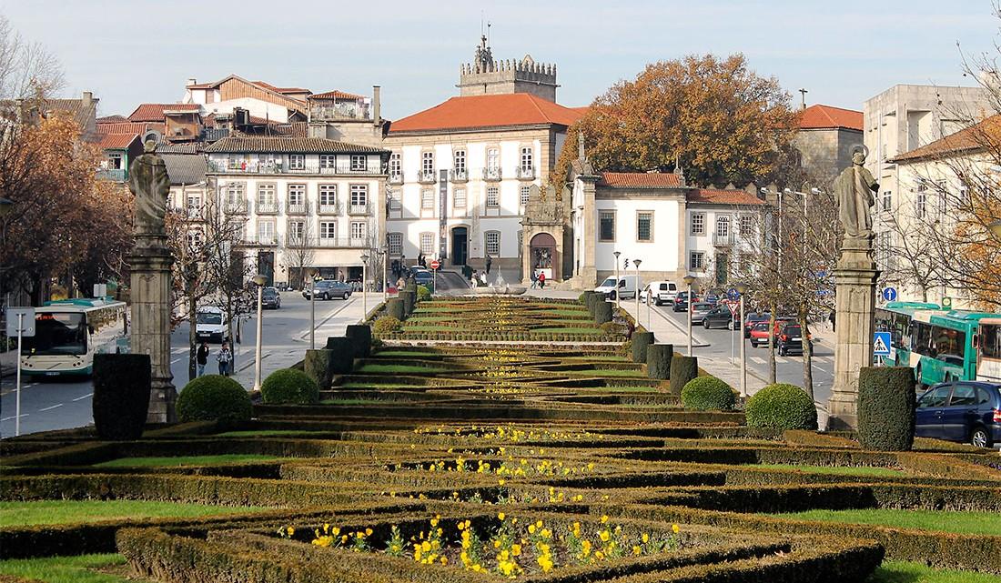 Avenida no centro histórico de Guimarães, com castelo ao fundo.