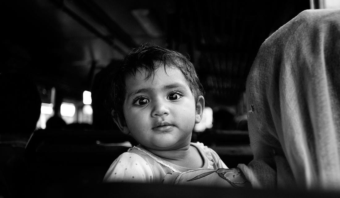 criança ao colo em comboio na Índia