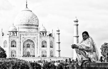 mulher sobre muro junto ao Taj Mahal