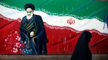 Mulher a passar junto a mural com Khomeini no Irão