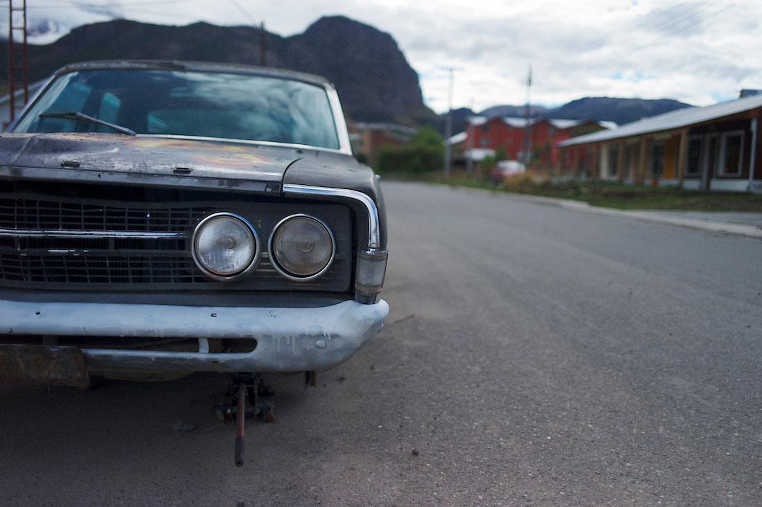 carro antigo abandonado, em estrada junto a casas vermelhas