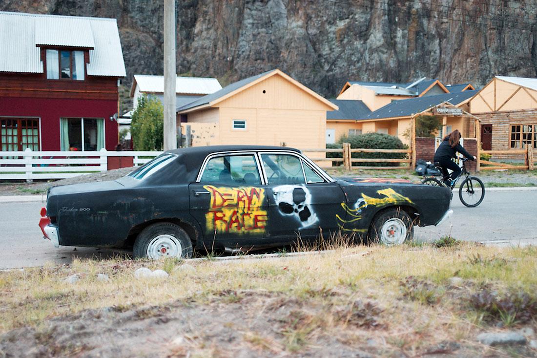 carro com graffitis junto a zona residencial