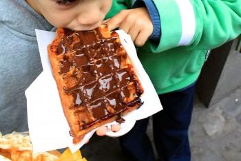 Família a comer um waffle com chocolate em Bruxela