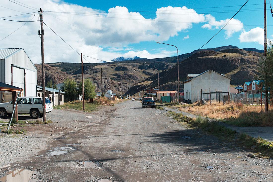 estrada terra batida com casas de madeira, junto a montanhas