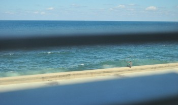 Por entre as frestas dos taipais vê-se o saxofinista que para o mar ensaia a sua melodia.