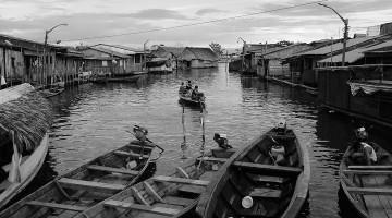 canal com canoas e várias casas de madeira em Iquitos