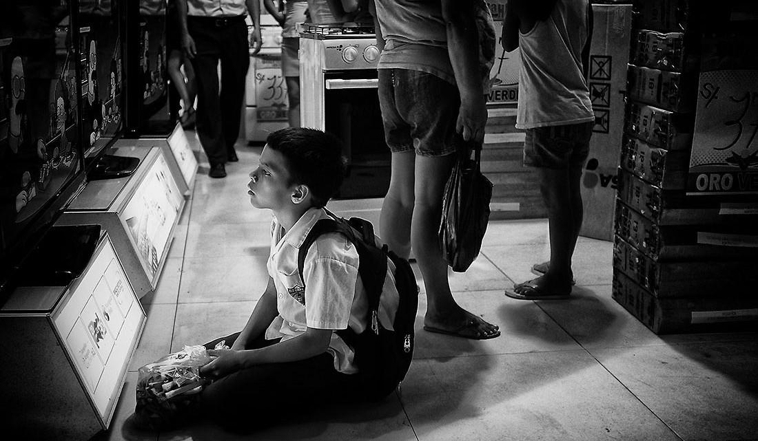 criança a ver televisão no chão de uma loja