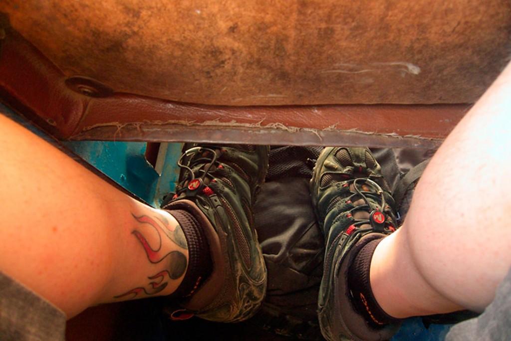 Pernas de passageiro entre os bancos de um autocarro em myanmar