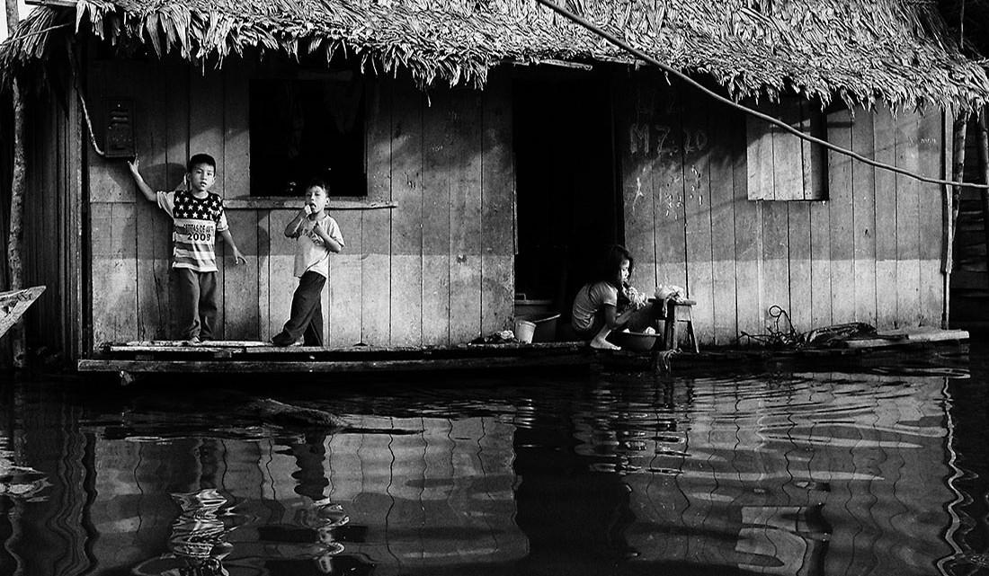 crianças junto a casa de madeira no bairro de bélen, Iquitos