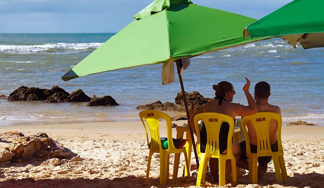 casal sob chapéus de sol, sentado em cadeiras de plástico, no morro são paulo, brasil