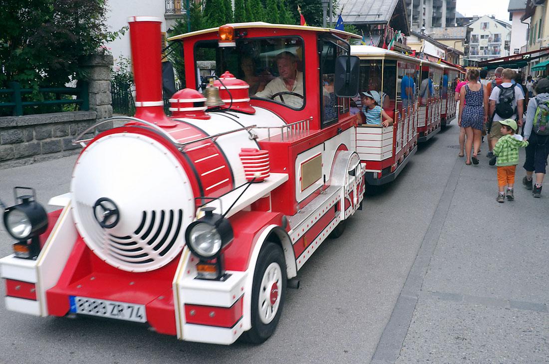 comboio vermelho e branco transporta turistas no centro de chamonix