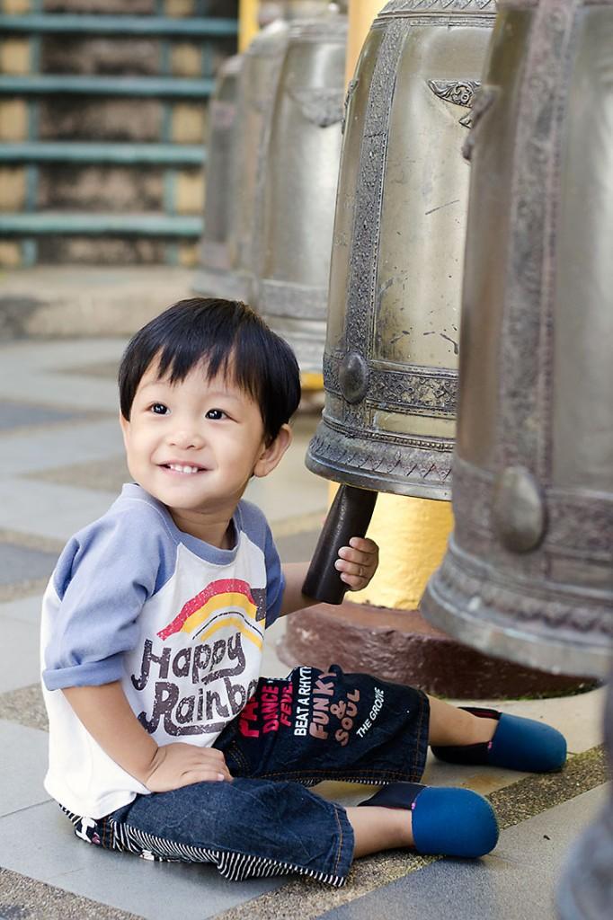 criança tailandesa a brincar com sinos de Wat Doi Suthep