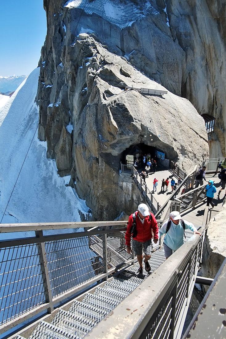 Turistas sobem escadas que levam ao complexo turístico instalado no topo da Aiguille du Midi