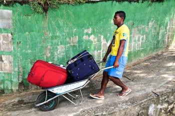 homem com carrinho de mão a transportar malas