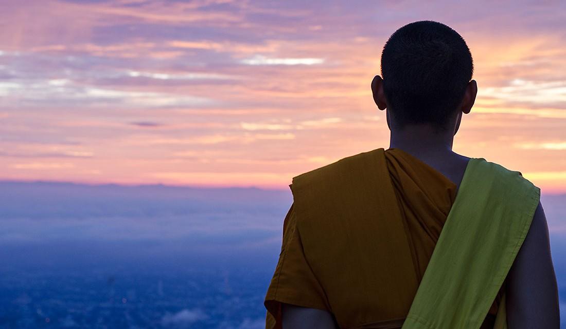monge budista que observa o pôr-do-sol