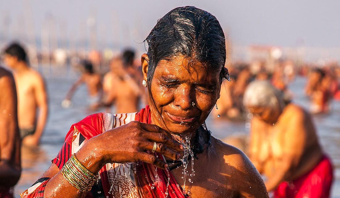 água escorre pelo corpo de uma mulher que acaba de mergulhar nos rios do sangam