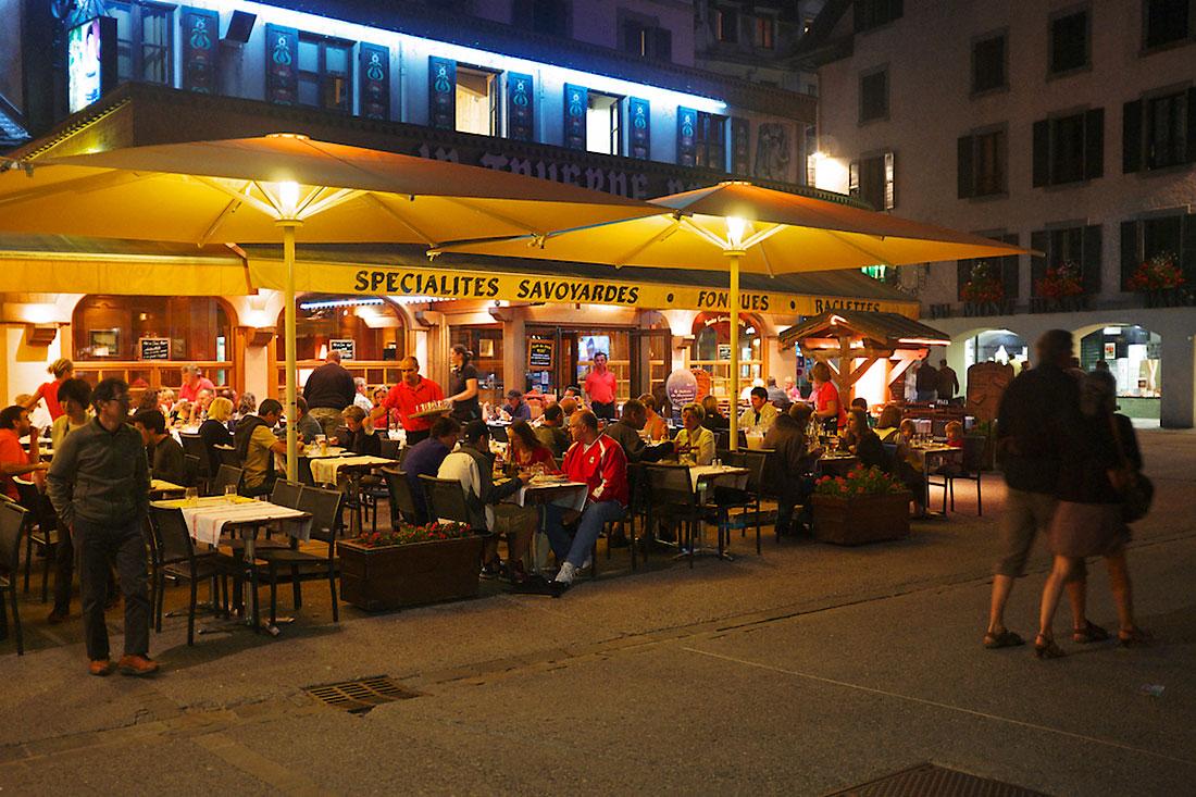 turistas e habitantes locais preparam-se para jantar numa esplanada de chamonix