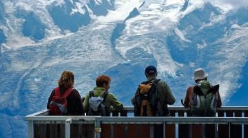 turistas contemplam o maciço do Monte Branco a partir da face oposta do vale de Chamonix