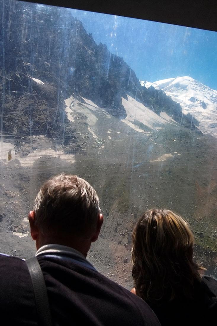 casal de turistas observa o maciço do Monte Branco do interior de uma cabine de teleférico