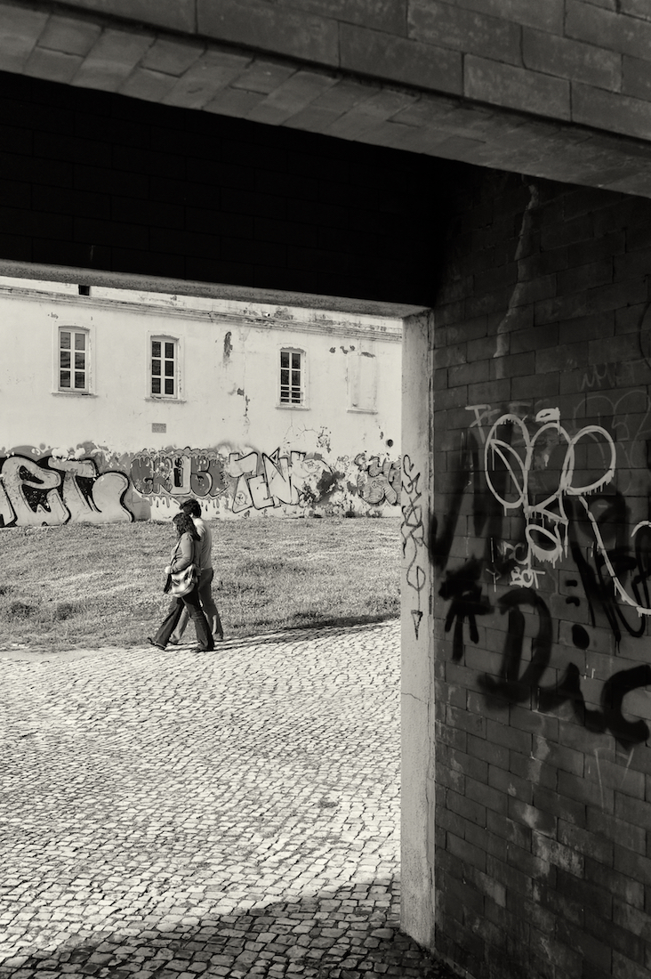 casal de pessoas junto edifícios degradados com graffitis