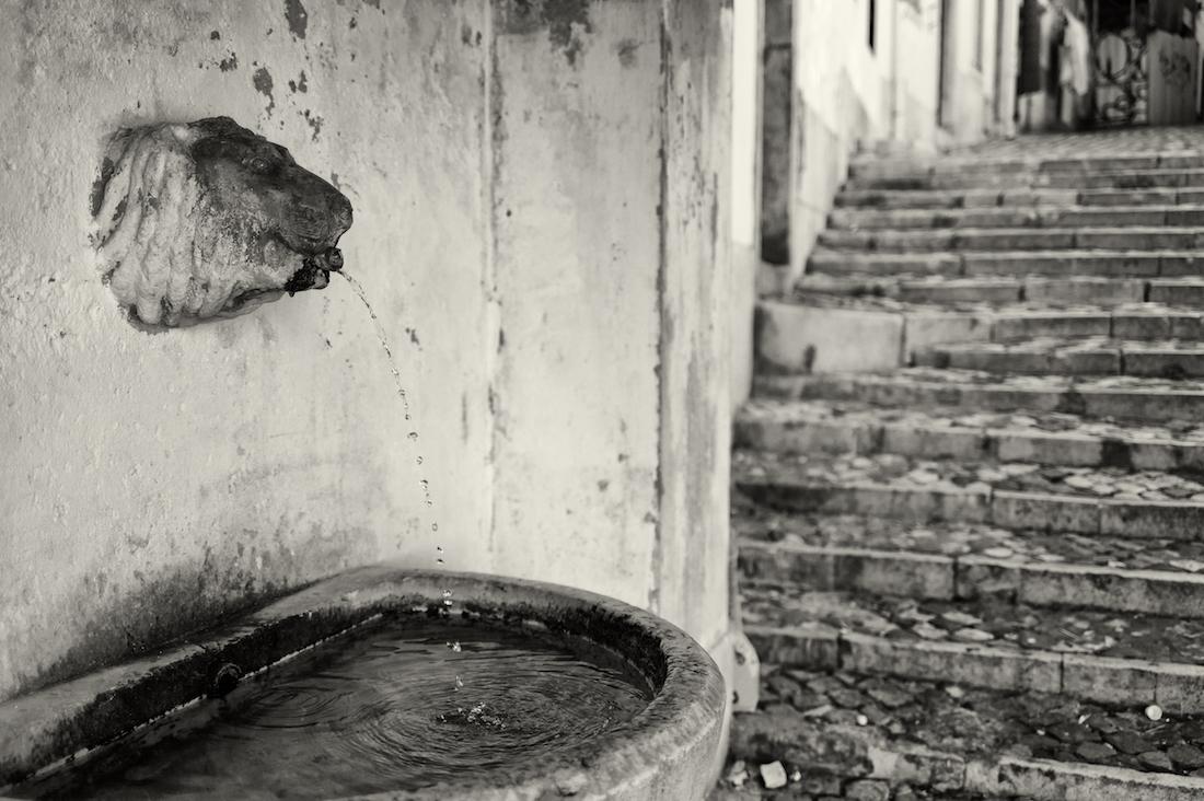 fontanario com bica em forma de leão em rua de Alfama