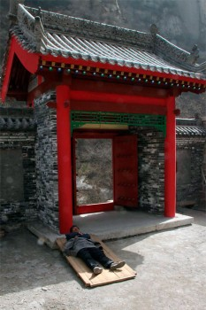 Trabalhador da construção a dormir à sombra da entrada de um templo