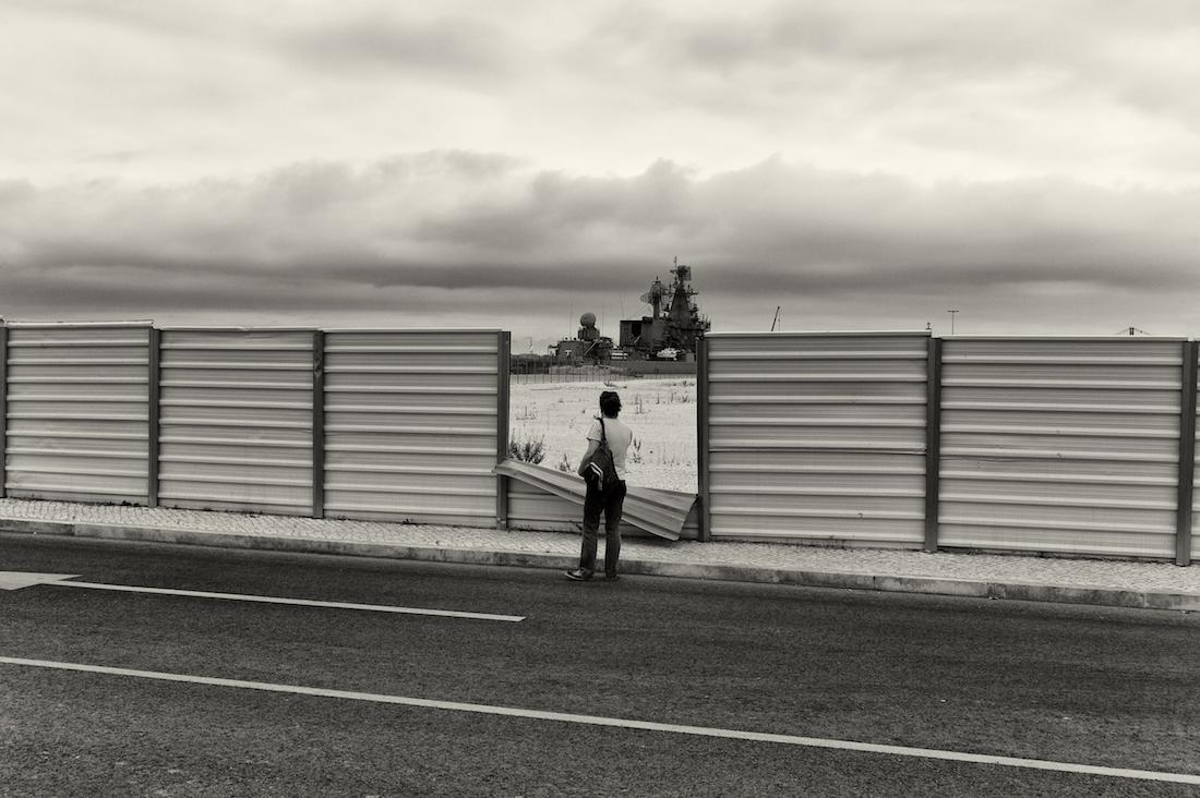 homem a observar navio de guerra através de cerca