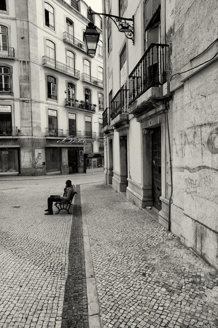 homem ao telemóvel em banco de jardim na baixa de Lisboa