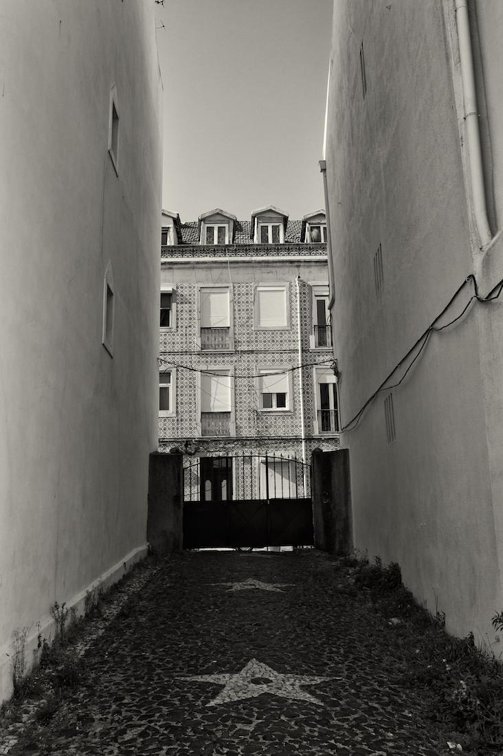 portão de ferro em rua estreita de Lisboa