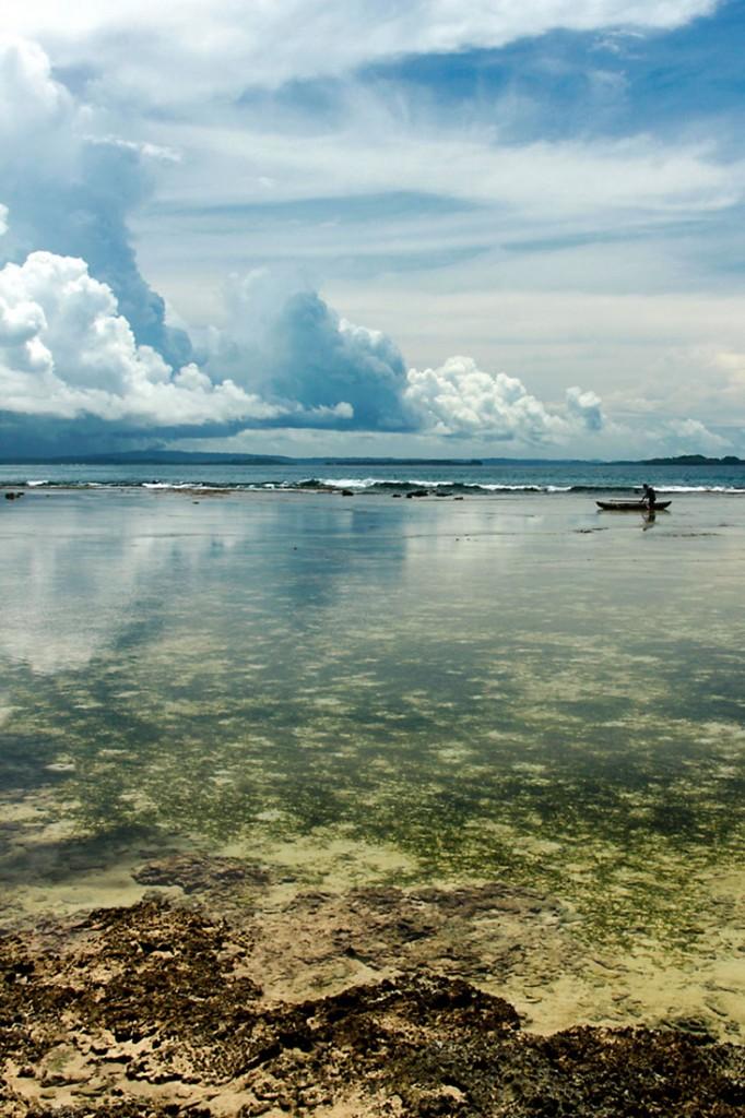 Junto à zona de corais, um pescador rema no mar