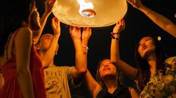 homens e mulheres tailandesas iluminados por um balão de ar quente durante o festival Loi Krathong
