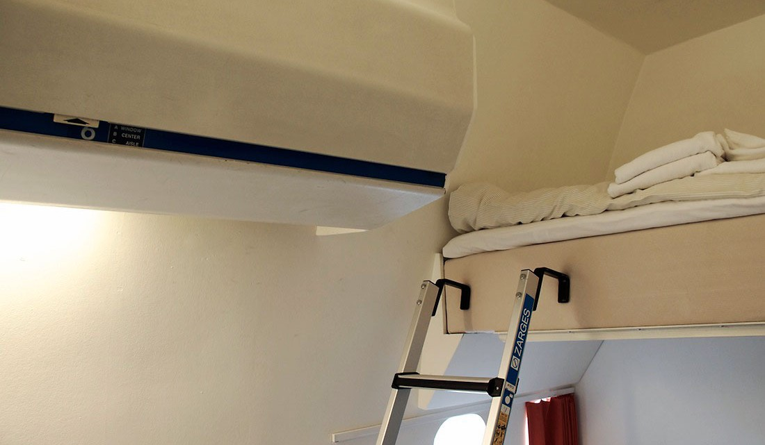pormenor de um beliche no hostel Jumbo Stay e antigos compartimentos de bagagem de mão