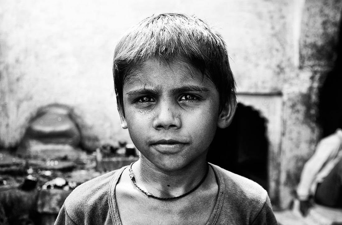 criança indiana na rua com colar ao pescoço