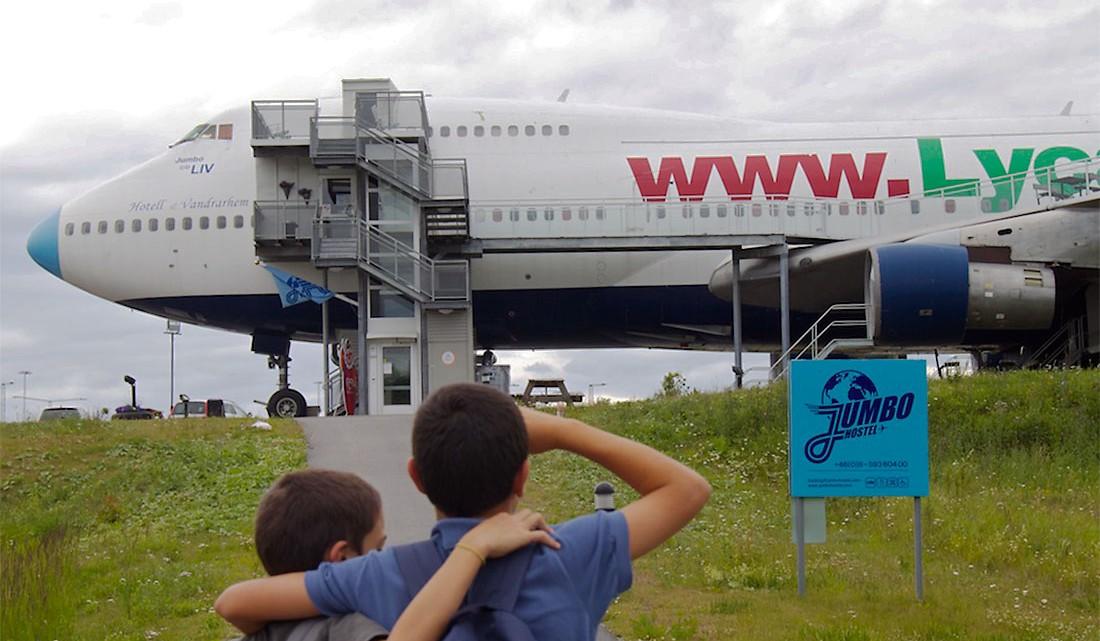 crianças junto à entrada do jumbo stay, um avião transformado em hostel