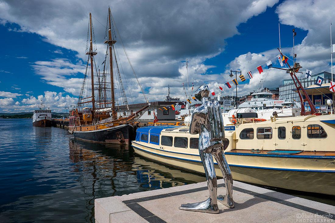 estátua de mergulhador e barcos no cais maritimo de Oslo