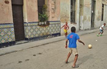 Meninos que jogam à bola numa rua de Centro Havana