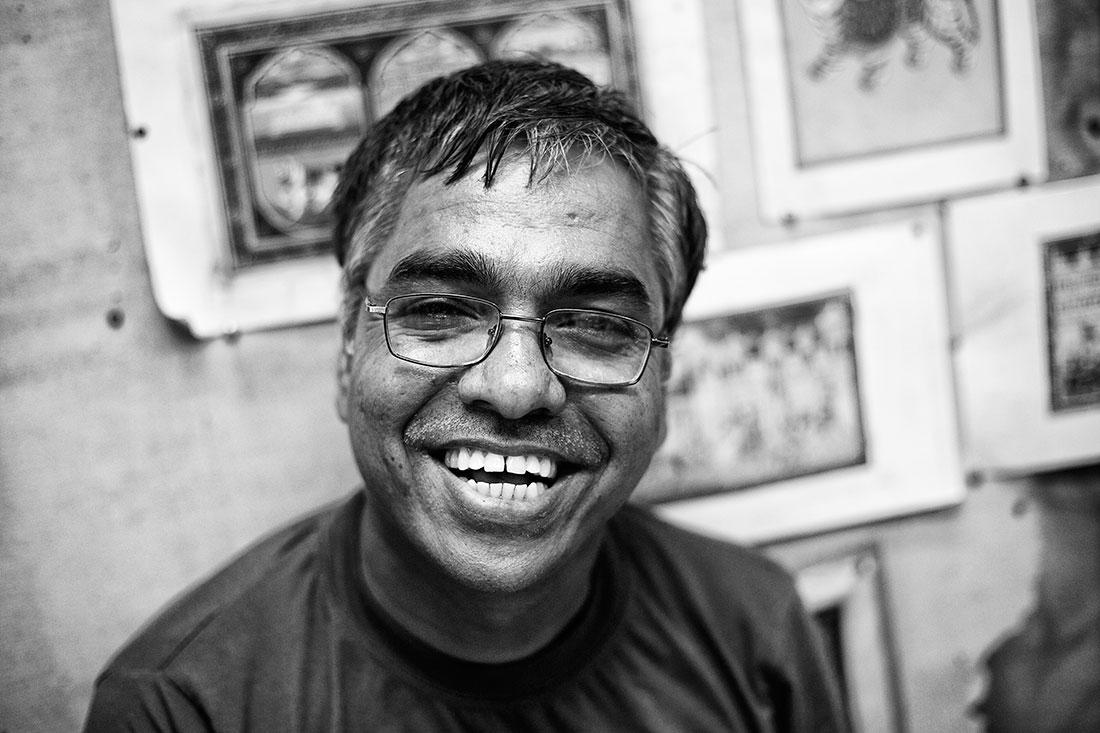homem indiano com óculos e um grande sorriso