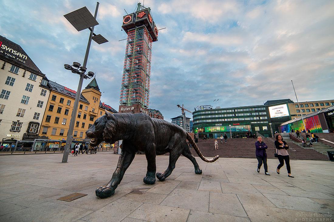escultura e pessoas na praça da Estação Central de Oslo