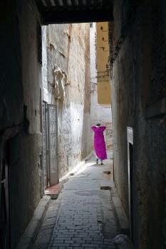 mulher que caminha numa rua estreita da medina de fez