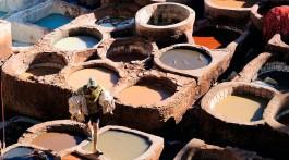 homem que caminha sobre bordas dos tanques de tingimento de curtumes na cidade de Fez