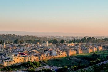 muralhas e medida da cidade de Fez, em Marrocos, iluminadas pela luz amarelada do pôr-do-sol